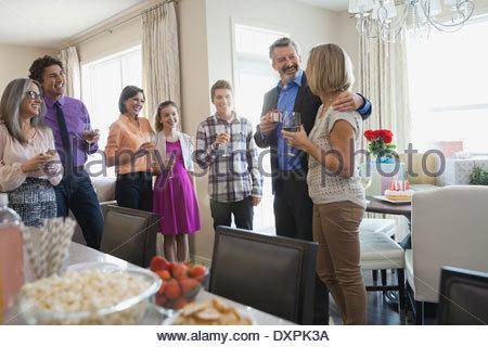 La famiglia e gli amici sorseggiando bevande alla festa di compleanno Foto Stock