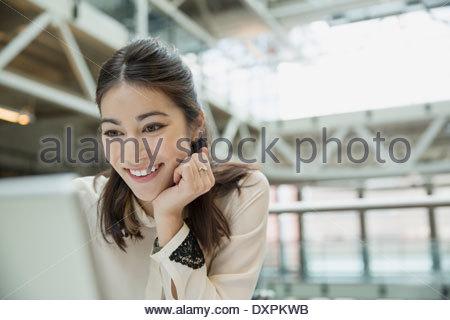 Felice imprenditrice utilizzando laptop Foto Stock