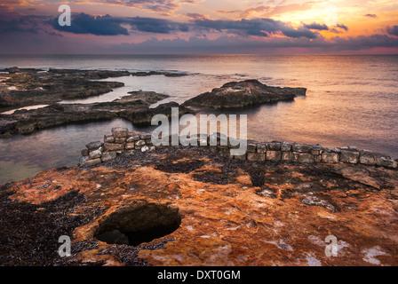 Tramonto sul mare e la costa rocciosa con le antiche rovine di Mahdia, Tunisia Foto Stock