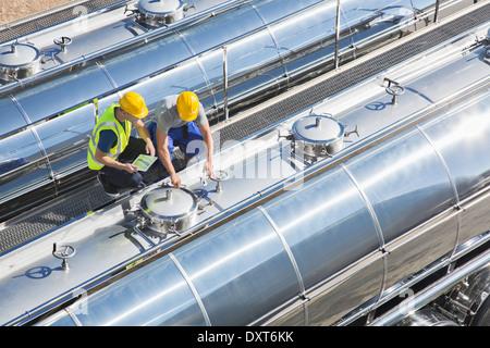 I lavoratori sulla piattaforma superiore in acciaio inox autocisterna per il latte Foto Stock