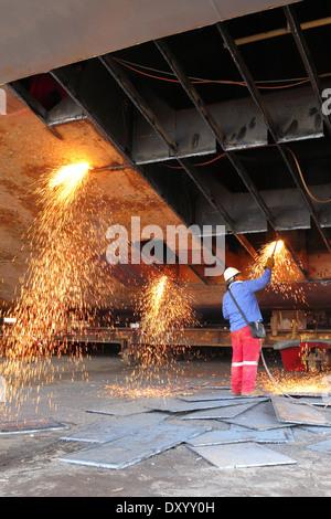 Le scintille volano come acciaio viene tagliata da un vecchio chiatta da un ossi-acetilene torcia presso un cantiere in Malaysia. Foto Stock