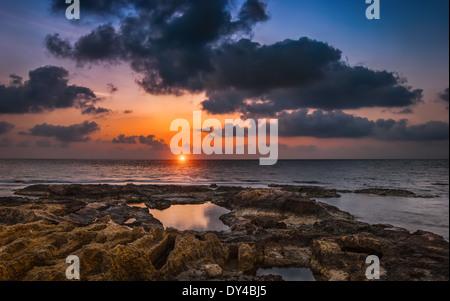 Nuvoloso Tramonto sul mare e la spiaggia rocciosa Foto Stock