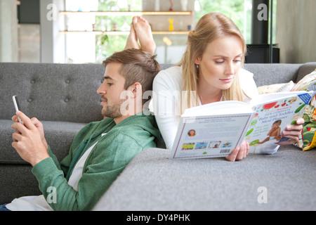 L'uomo utilizza lo smartphone e la donna la lettura di un libro sul divano