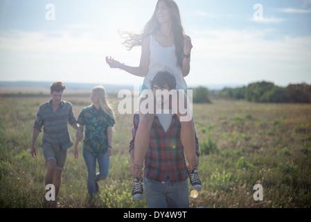 Gli amici passeggiando nel campo, uomo donna che porta sulle spalle Foto Stock