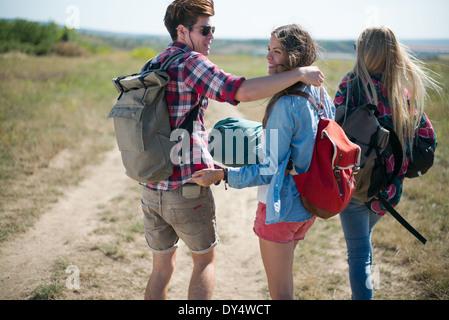Tre amici a piedi su sterrato con zaini Foto Stock