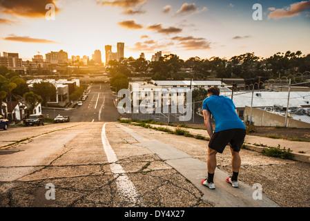 Giovane maschio runner prendendo una pausa in cima ad una ripida collina della città Foto Stock