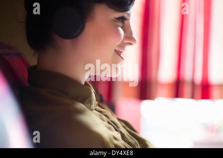 Giovane donna seduta su un divano, ascoltando la musica sulle cuffie Foto Stock