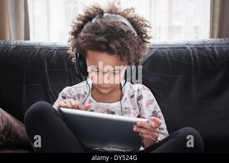 Ragazza seduta sul divano con tavoletta digitale e cuffie Foto Stock