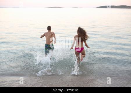 Coppia giovane in esecuzione in mare insieme, Orebic, Croazia Foto Stock