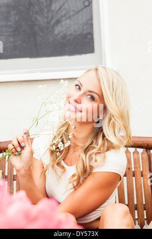 Giovane donna fiori di contenimento Foto Stock