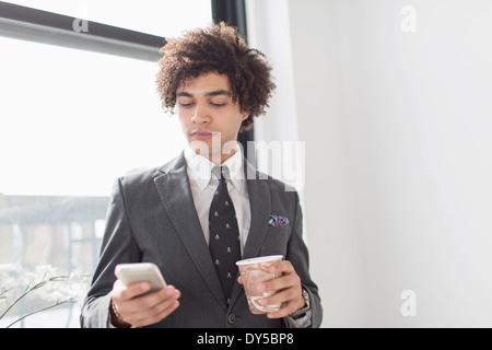 Giovane uomo tramite telefono cellulare con caffè Foto Stock