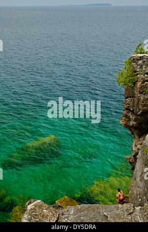 Metà donna adulta accovacciato sulle rocce a costa, Toronto, Ontario, Canada Foto Stock