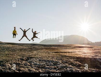 Tre giovani femmine escursionisti jumping mezza aria su roccia, Squamish, British Columbia, Canada Foto Stock