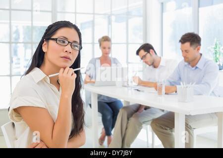 Casual imprenditrice pensando durante una riunione Foto Stock
