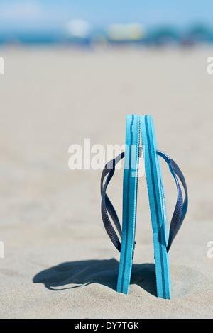 Coppia di luce blu flip-flop in piedi nella sabbia Foto Stock