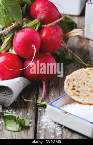 Fresche ravanelli bagnato con sale marino e pane su un vecchio tavolo in legno Foto Stock