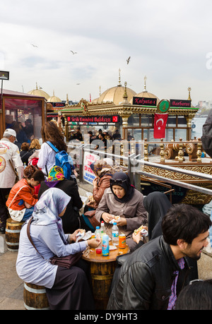 La gente del posto e turisti di mangiare da imbarcazioni di vendita del pesce panini vicino al Ponte di Galata, Foto Stock