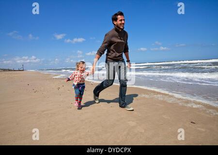 Un padre e figlia che corre lungo la spiaggia a Horsey sulla costa di Norfolk. Foto Stock