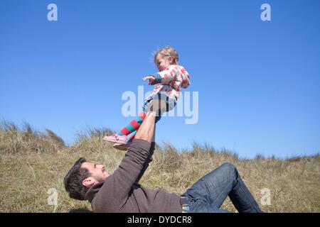 Un padre giocando con sua figlia su Horsey dune di sabbia sulla costa di Norfolk. Foto Stock