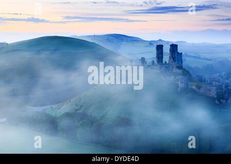 Corfe Castle nel Dorset sollevandosi al di sopra di early morning mist.