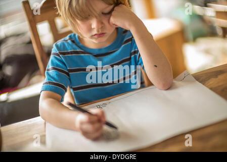 Sette anni di disegno del ragazzo al tavolo. Foto Stock