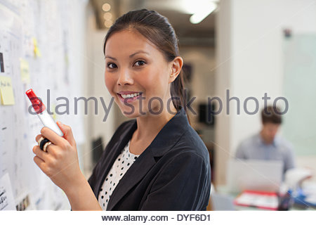 Sorridente imprenditrice lavagna anteriore in office Foto Stock