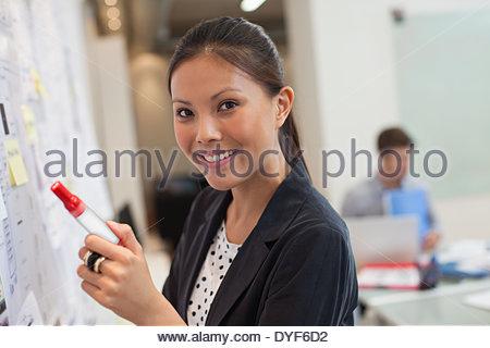 Sorridente imprenditrice lavagna anteriore in office Foto Stock