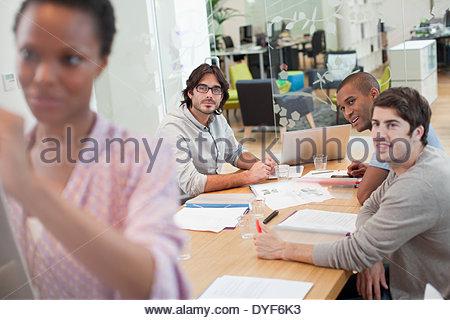 Donna sorridente scrivere sulla lavagna della sala conferenze Foto Stock