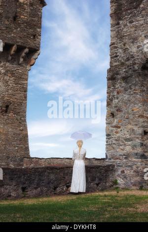 Una donna in un periodo bianco vestito è di fronte ad un muro di pietra con un ombrellone