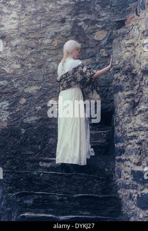 Una donna in un periodo bianco vestito è in piedi sul vecchio di gradini di pietra