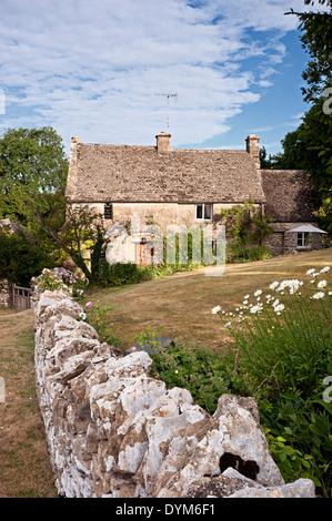 Cotswold cottage in pietra con parete e giardino in estate Foto Stock