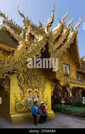 Turisti che si siedono di fronte al wc dorato casa a Wat Rong Khun, bianco tempio, dall'architetto Chalermchai Kositpipat Foto Stock