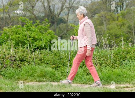 Signora anziana con un bastone passeggiate in campagna in primavera nel Regno Unito. Foto Stock
