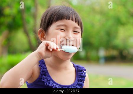 Felice bambina mangiare ghiaccioli al DST Foto Stock