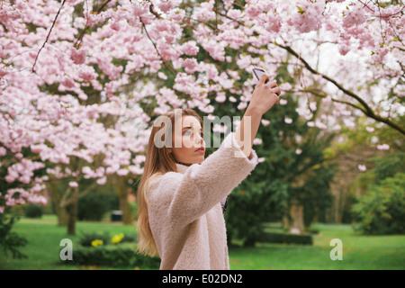 Giovane donna caucasica dipinge sbocciare fiori con il suo telefono cellulare. Donna attraente fotografare fiori Foto Stock