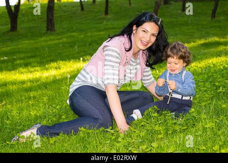 Allegro madre e bambino figlio seduto in erba e divertirsi insieme Foto Stock