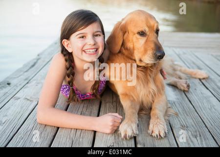 Una giovane ragazza e un golden retriever cane giacente su un pontile. Foto Stock