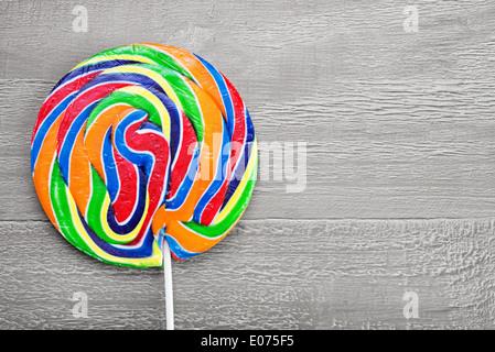 Vera e propria spirale colorata lollipop su legno tabella vintage Foto Stock