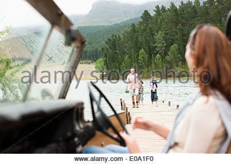 Donna seduta del veicolo vicino al lago Foto Stock