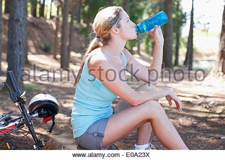 Donna acqua potabile in foresta Foto Stock