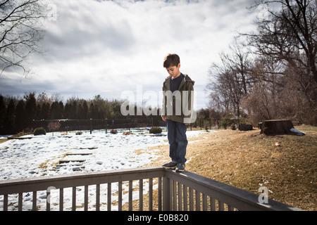 Bilanciamento del ragazzo sulla sommità del recinto nel parco Foto Stock
