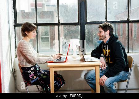 Maschio e femmina dei progettisti che lavorano su computer portatili in studio Foto Stock