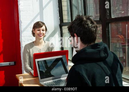 Maschio e femmina designers chattare su notebook in studio Foto Stock