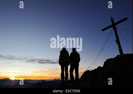 Giovane donna e giovane uomo godersi il tramonto al vertice di Risserkogel, Prealpi bavaresi, montagne Mangfall, Foto Stock