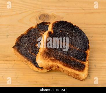 Tostare il pane divenne burntly. Burntly toast con i dischi e la prima colazione., Toastbrot wurde beim toasten verbrannt. Foto Stock