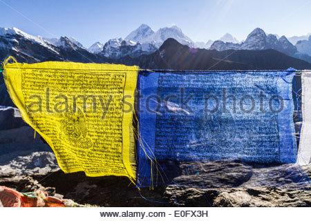 Giallo e blu la preghiera buddista bandiere dell'Everest, sul Nuptse e Makalu Da Gokyo Ri, Himalaya, Nepal Foto Stock