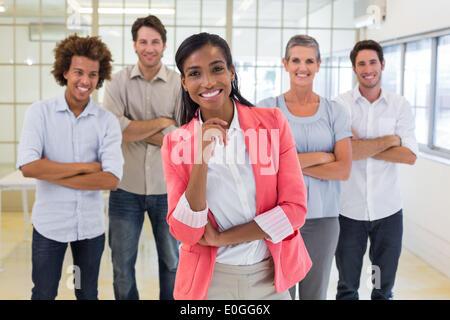 Ben vestito i lavoratori con i bracci ripiegati sorridente in telecamera Foto Stock