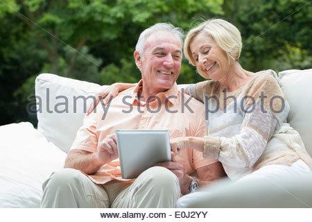 Coppia senior con tavoletta digitale sul divano per esterni Foto Stock