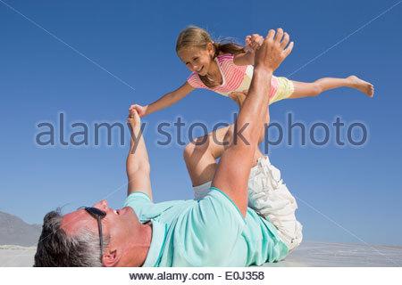 Padre figlia di sollevamento di sunny beach Foto Stock
