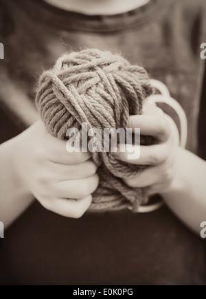 Close up della bambina tenendo una palla di filato nelle sue mani Foto Stock